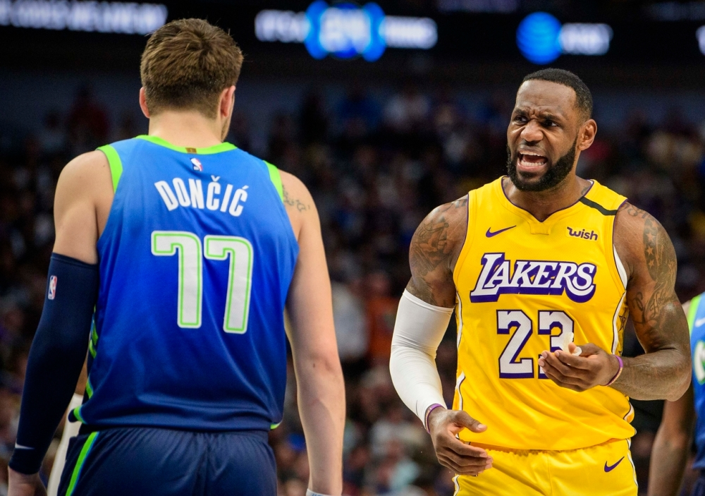LeBron James celebrates a play in front of Luka Doncic