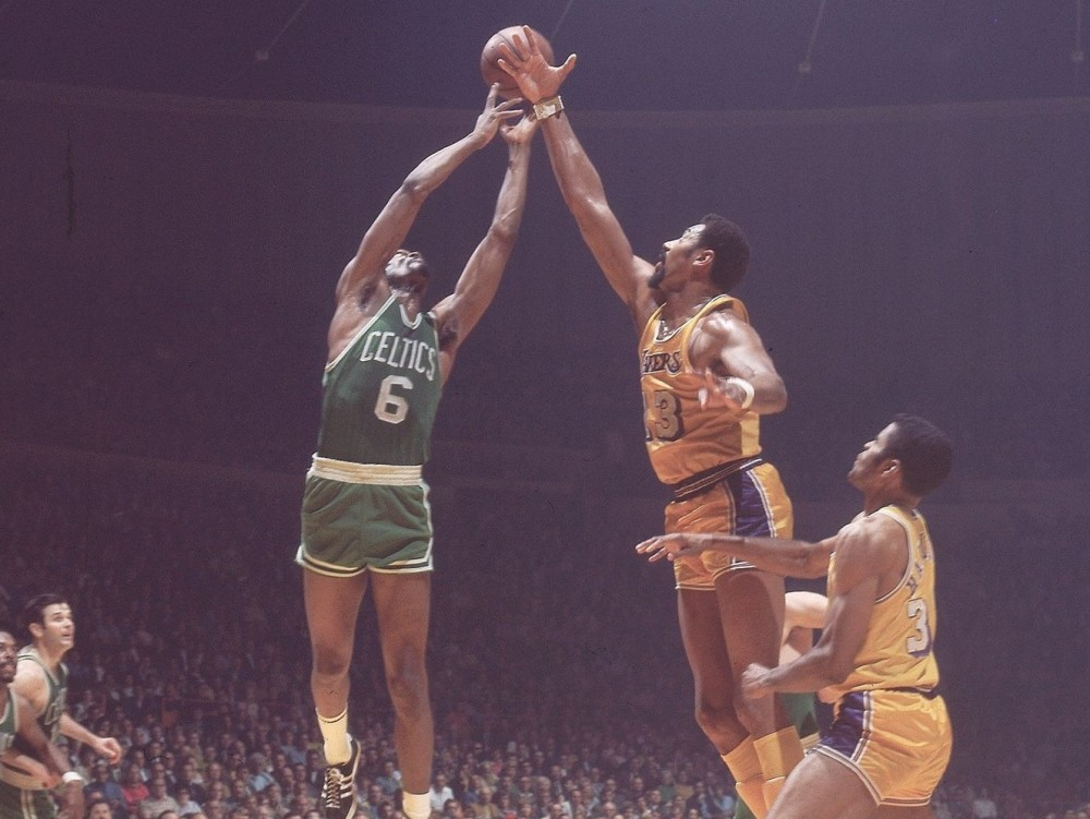 Wilt Chamberlain and Bill Russell fight for a rebound