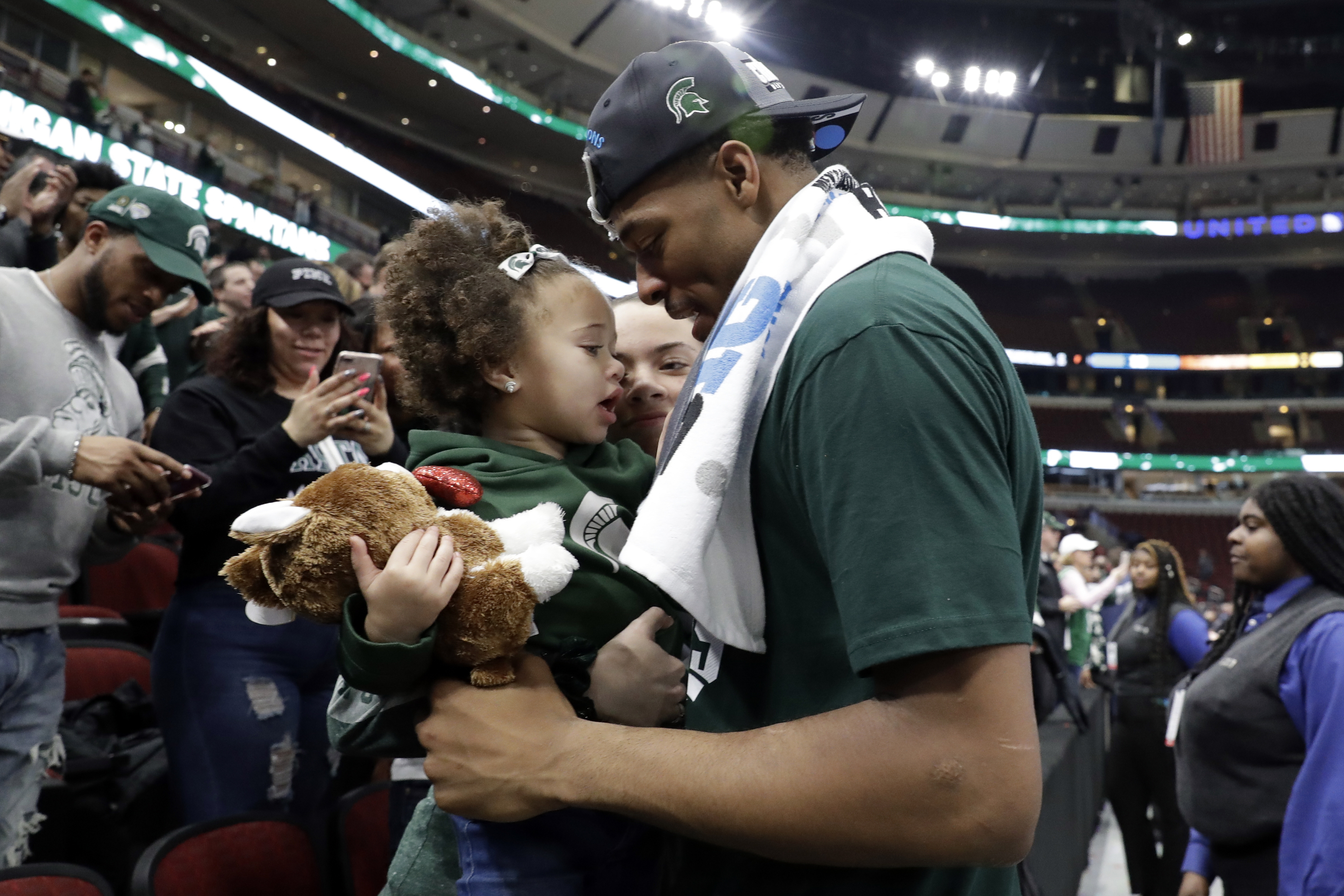 Michigan State's Xavier Tillman celebrates with his daughter after defeating Michigan 65-60 in an NCAA college basketball championship game in the Big Ten Conference tournament, Sunday, March 17, 2019, in Chicago.