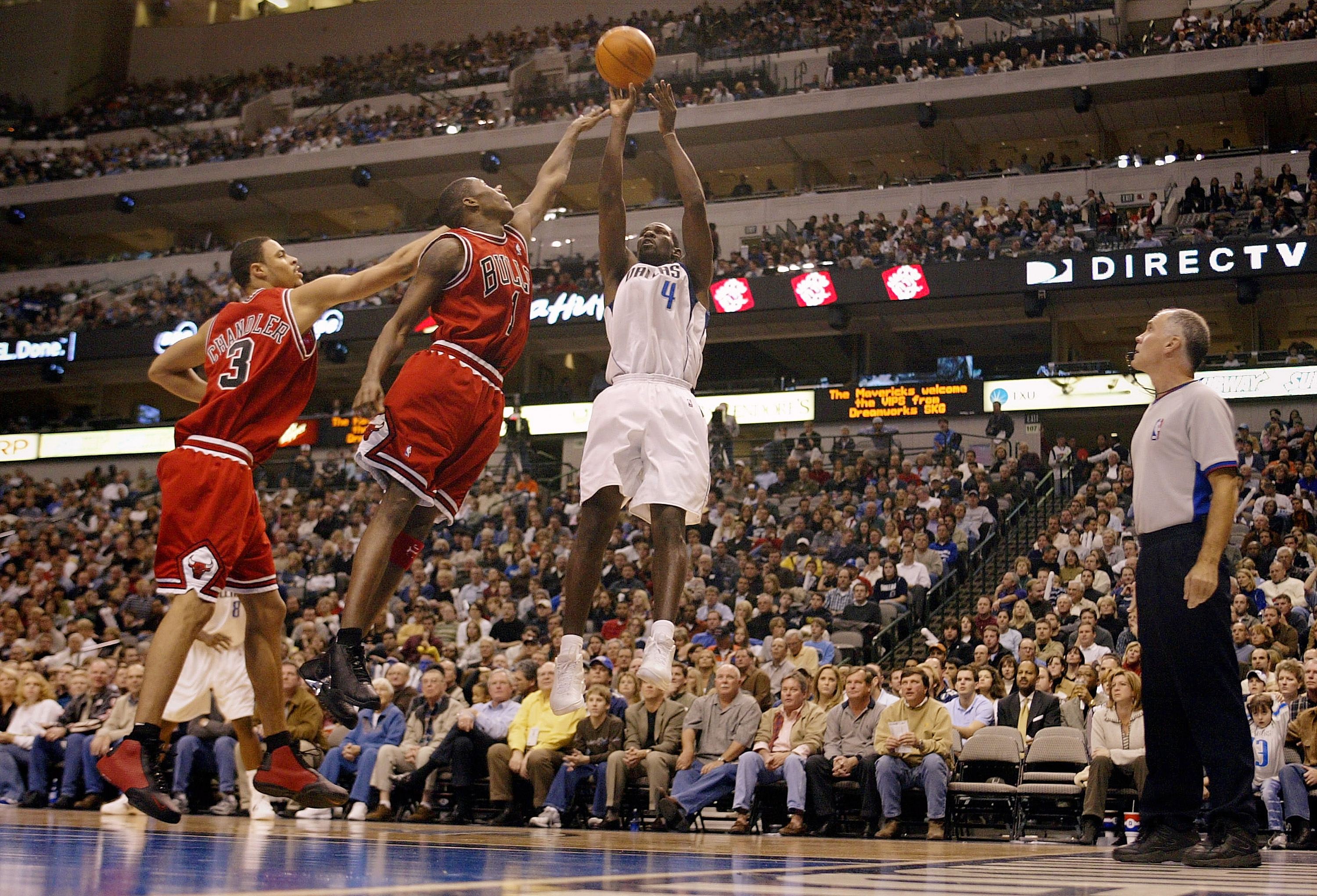 DALLAS - NOVEMBER 25: Guard Michael Finley #4 of the Dallas Mavericks puts up a shot against Jamal Crawford #1 and Tyson Chandler #3 of the Chicago Bulls in the second quarter November 25, 2003 at the American Airlines Center in Dallas, Texas. NOTE TO USER: User expressly acknowledges and agrees that, by downloading and/or using this Photograph, User is consenting to the terms and conditions of the Getty Images License Agreement.