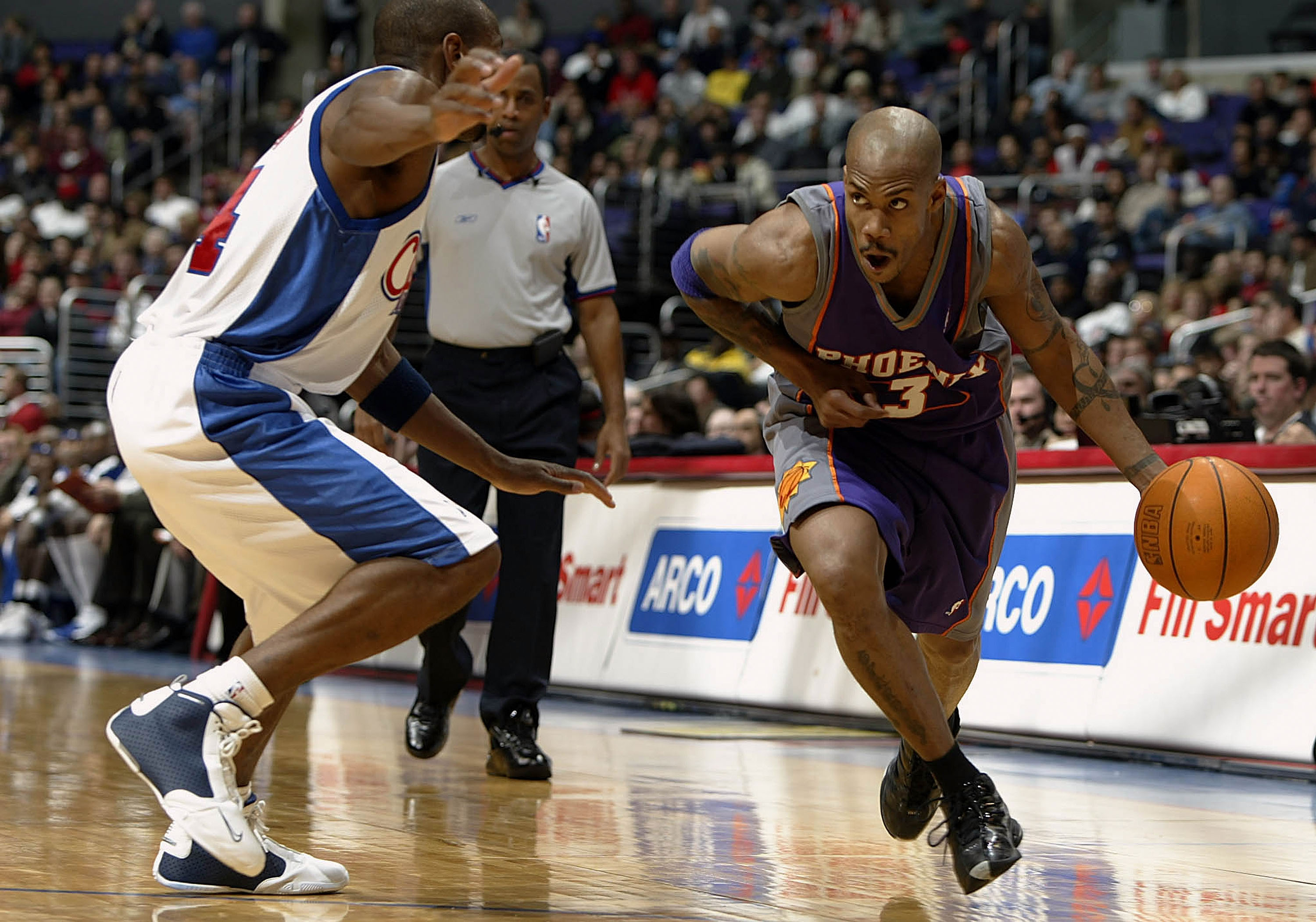 LOS ANGELES - DECEMBER 29: Stephon Marbury #3 of the Phoenix Suns drives past Doug Overton #24 of the Los Angeles Clippers during their game on December 29, 2003 at Staples Center in Los Angeles, California. The Suns won 113-105. NOTE TO USER: User expressly acknowledges and agrees that, by downloading and/or using this Photograph, User is consenting to the terms and conditions of the Getty Images License Agreement.