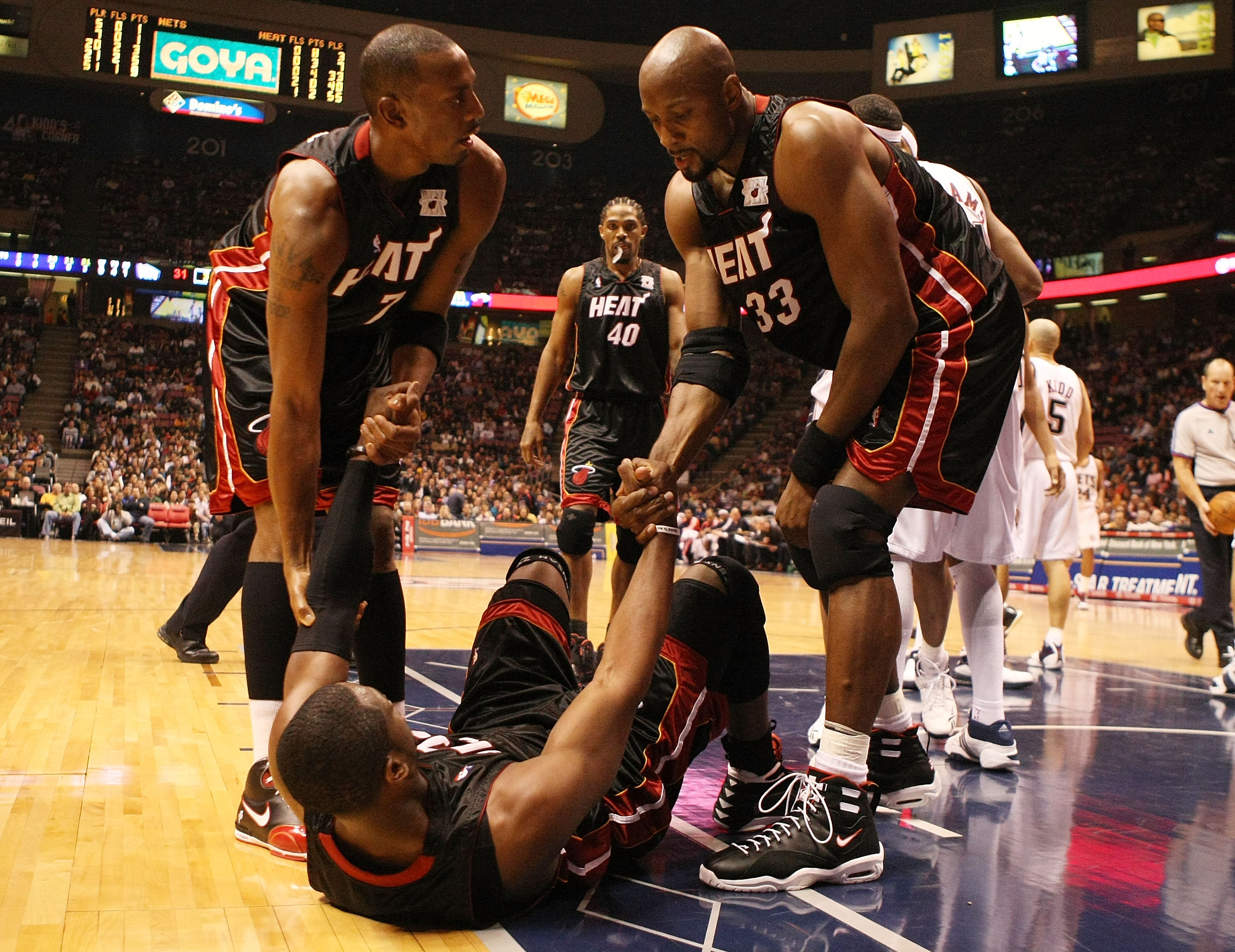 EAST RUTHERFORD, NJ - NOVEMBER 17: Dwyane Wade #3 of the Miami Heat is helped up by Anfernee Hardaway #7 and Alonzo Mourning #33 against the New Jersey Nets during their game on November 17, 2007 at the Izod Arena in East Rutherford, New Jersey.