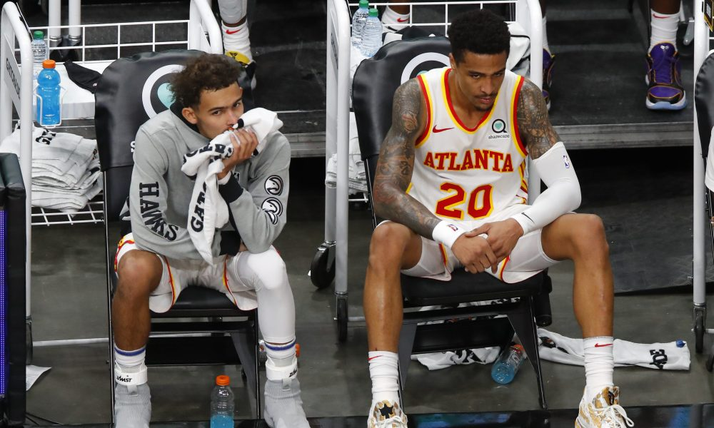 ATLANTA, GA - JANUARY 02: Trae Young #11 and John Collins #20 of the Atlanta Hawks look on from the bench during the second half against the Cleveland Cavaliers at State Farm Arena on January 2, 2021 in Atlanta, Georgia.