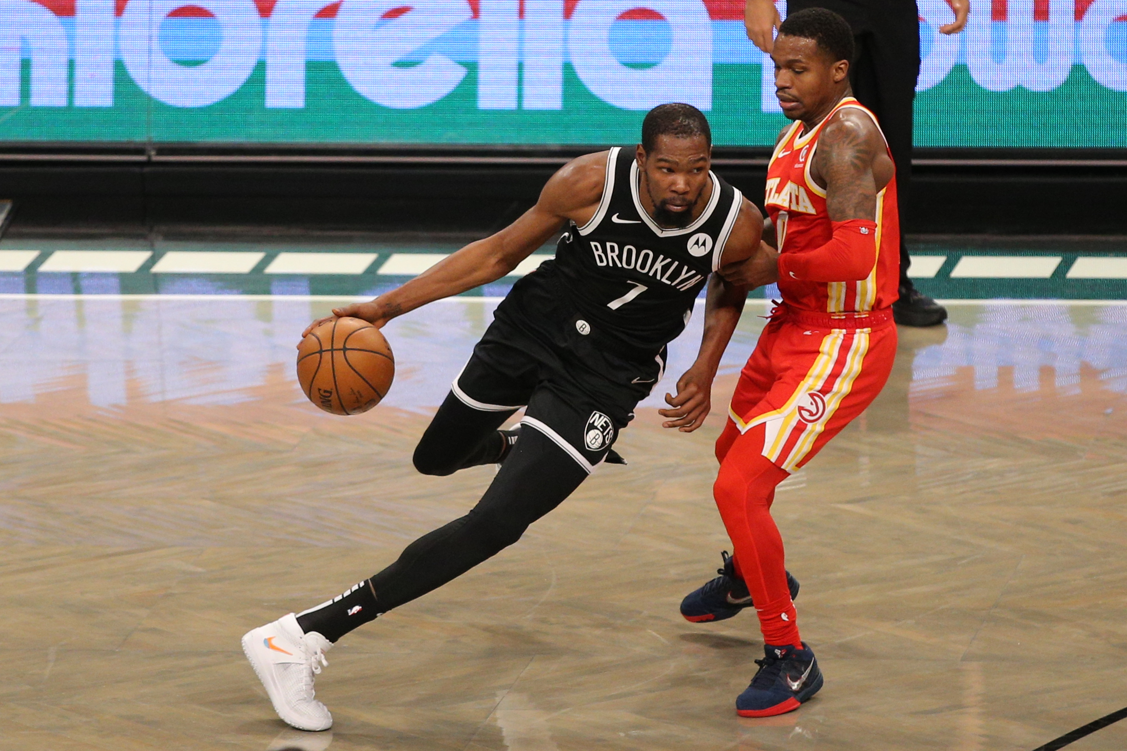 Jan 1, 2021; Brooklyn, New York, USA; Brooklyn Nets small forward Kevin Durant (7) drives the ball around Atlanta Hawks point guard Brandon Goodwin (0) during the fourth quarter at Barclays Center