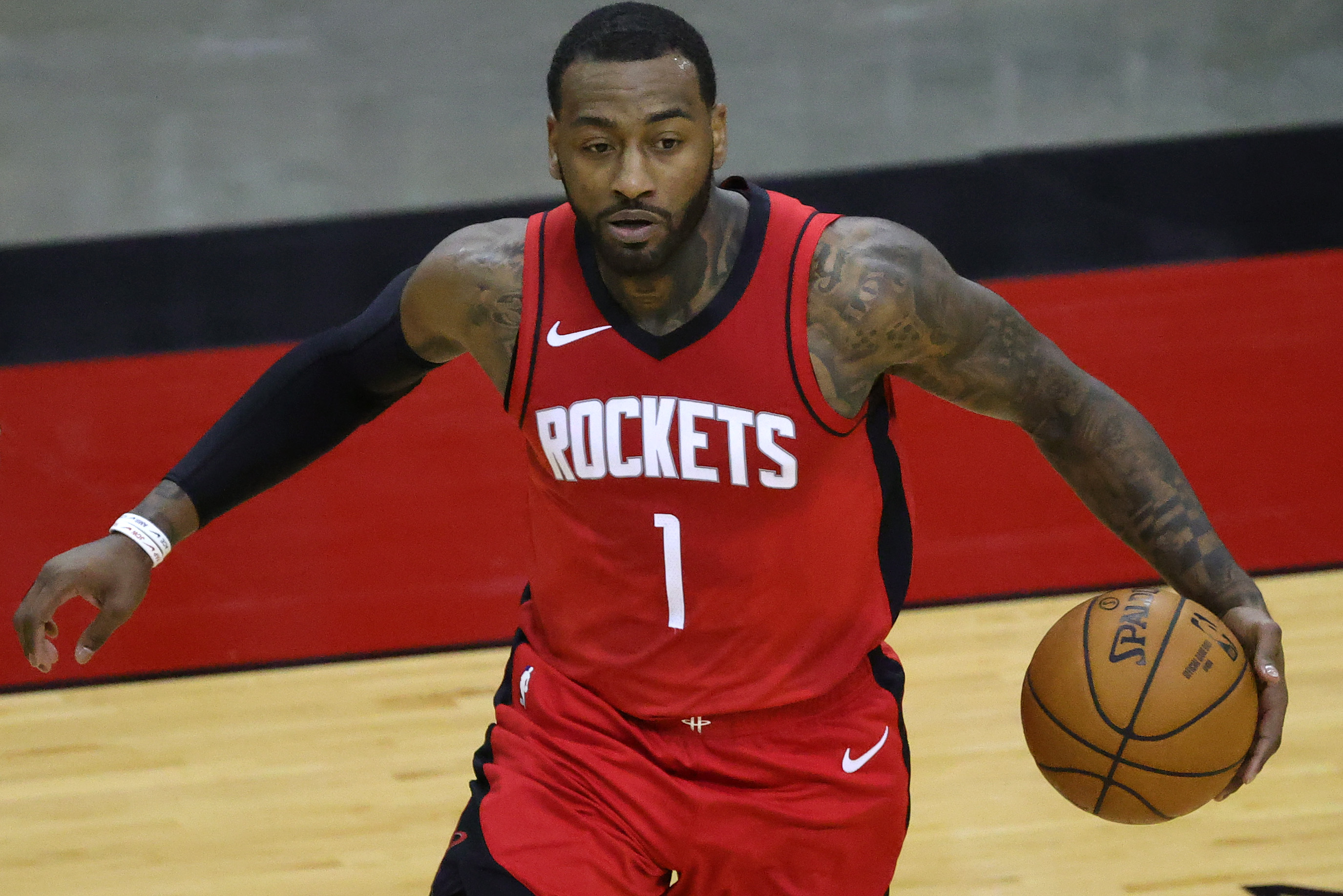 Jan 2, 2021; Houston, Texas, USA; John Wall #1 of the Houston Rockets controls the ball during the fourth quarter of a game against the Sacramento Kings at Toyota Center on January 02, 2021 in Houston, Texas.