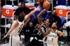 Los Angeles Clippers guard Lou Williams, center, shoots as Brooklyn Nets forward Joe Harris, left, and guard Bruce Brown defend during the first half of an NBA basketball game Sunday, Feb. 21, 2021, in Los Angeles.