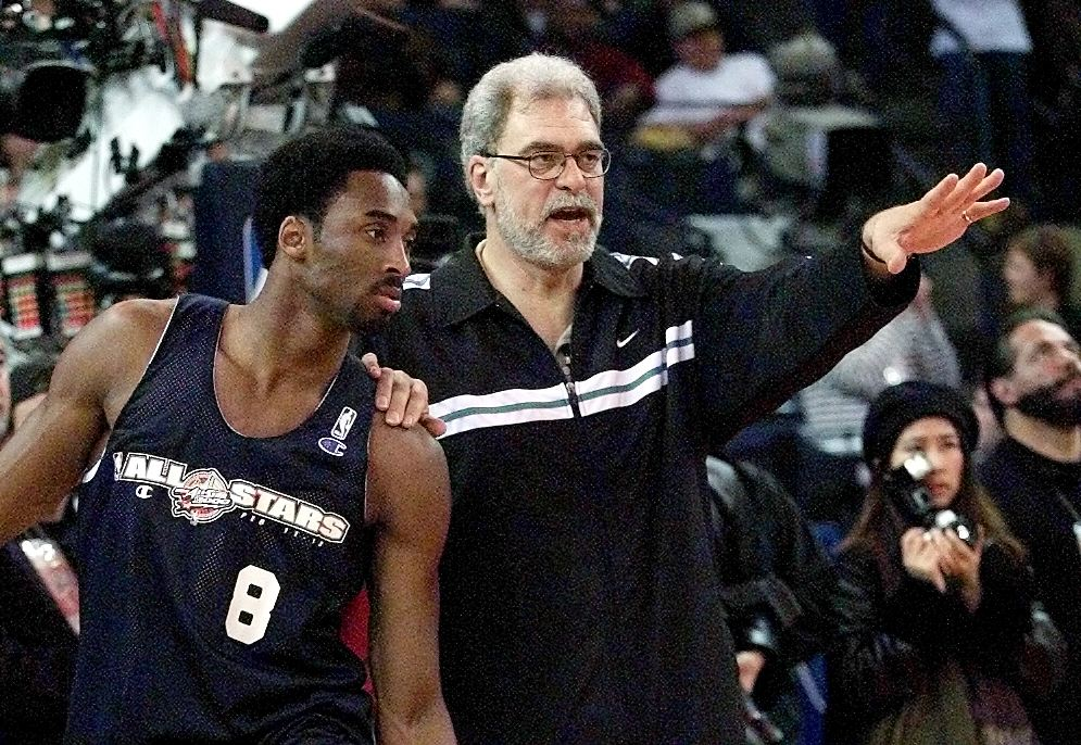 Los Angeles Lakers' player Kobe Bryant (L) gets instructions from coach Phil Jackson (R) at the NBA All-Star West team practice session 12 February 2000 at the Arena in Oakland, California. After an absence of one year the NBA All-Star game pitting the best of the East and West will be played 13 February 2000. (ELECTRONIC IMAGE) AFP PHOTO/Andy KUNO (Photo by ANDY KUNO / AFP)