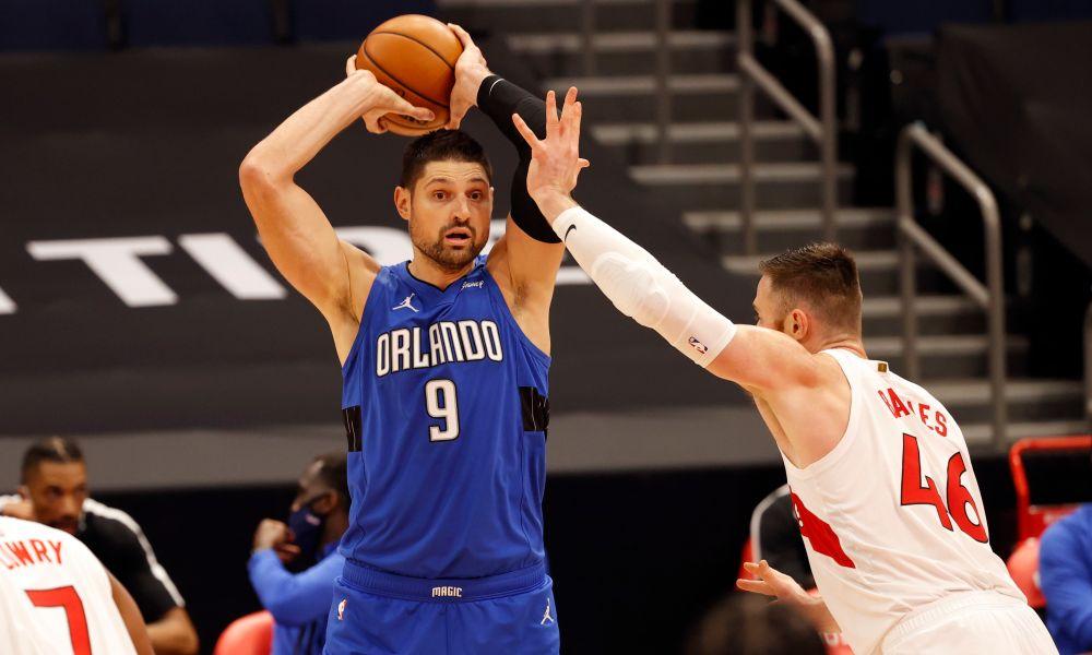 Jan 31, 2021; Tampa, Florida, USA; Orlando Magic center Nikola Vucevic (9) drives to the basket as Toronto Raptors center Aron Baynes (46) defends during the second half at Amalie Arena.