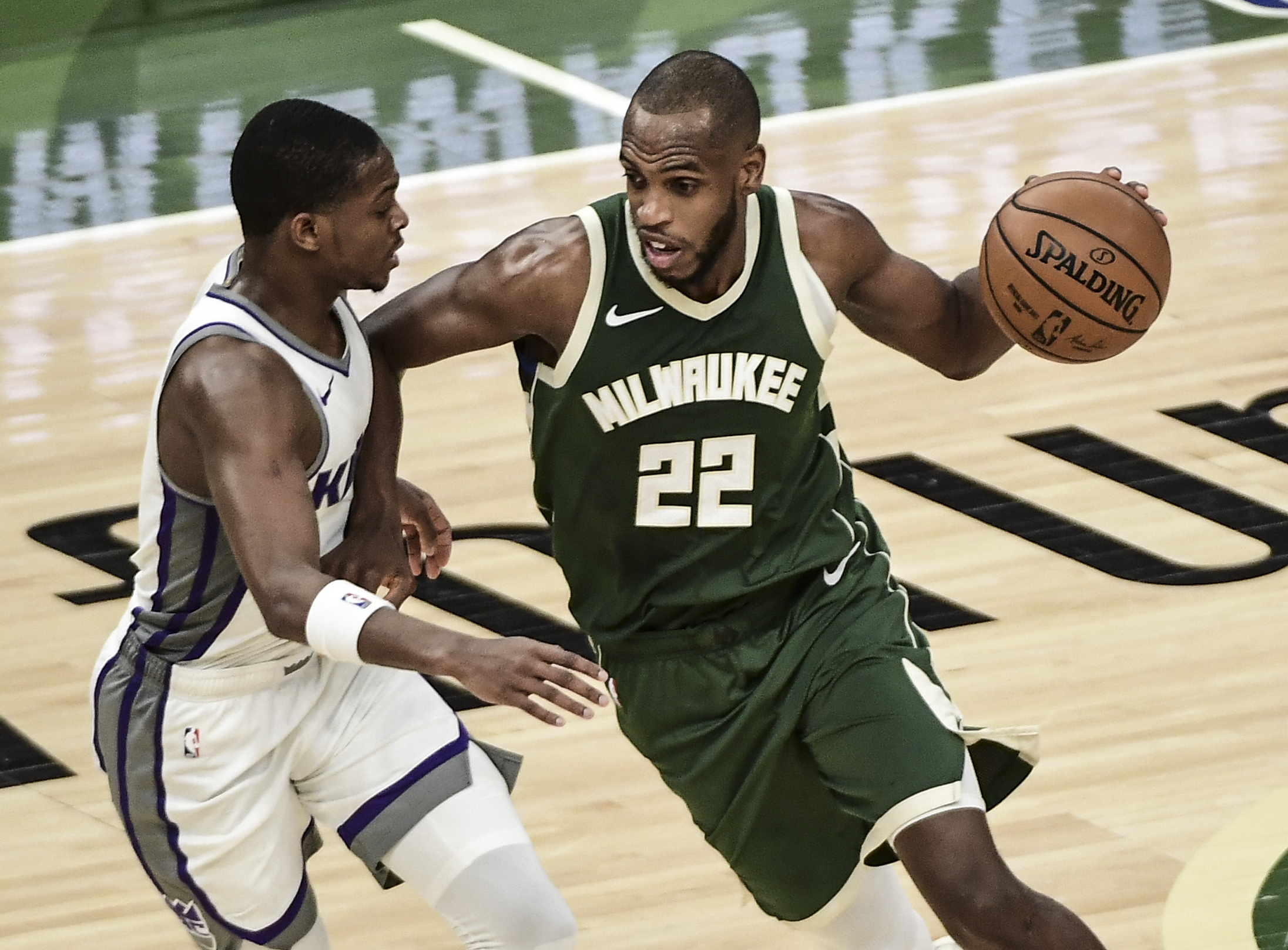 Feb 21, 2021; Milwaukee, Wisconsin, USA; Milwaukee Bucks forward Khris Middleton (22) drives for the basket against Sacramento Kings guard De'Aaron Fox (5) in the third quarter at Fiserv Forum.
