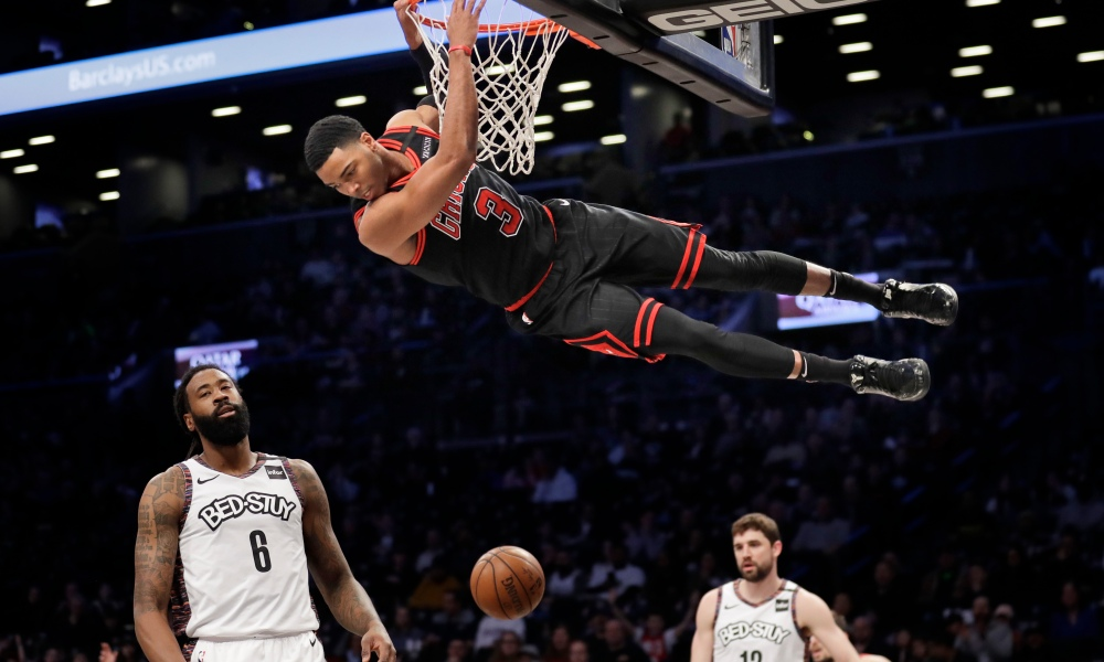 Chicago Bulls' Shaquille Harrison (3) hangs from the rim after dunking during the first half of an NBA basketball game against the Brooklyn Nets at the Barclays Center, Sunday, March 8, 2020, in New York.