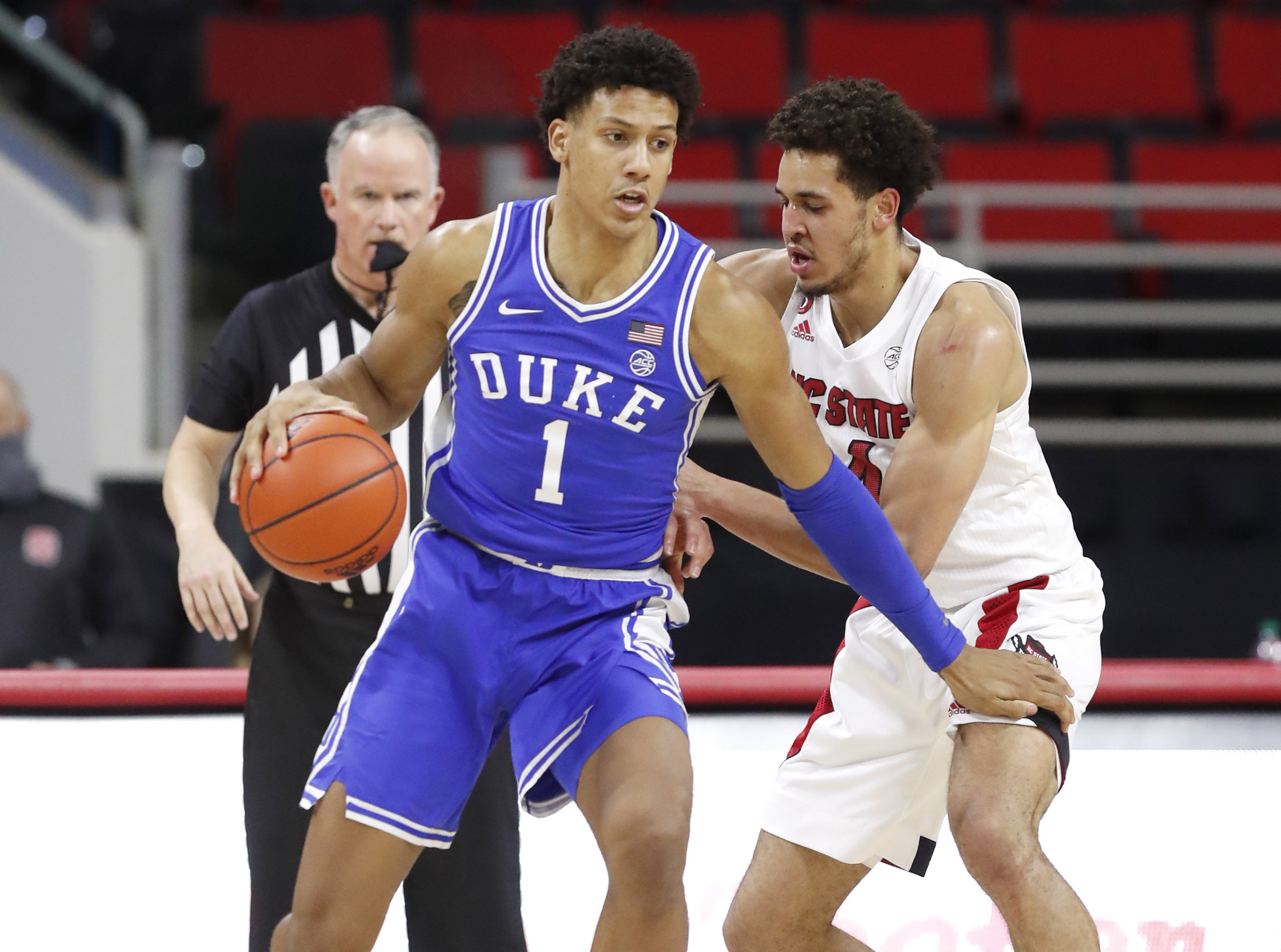 Duke's Jalen Johnson (1) looks for space as N.C. State's Jericole Hellems (4) defends during the first half of an NCAA college basketball game against North Carolina State in Raleigh, N.C., Saturday, Feb. 13, 2021.
