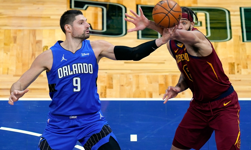 Orlando Magic center Nikola Vucevic (9) and Cleveland Cavaliers center JaVale McGee, right, go after a loose ball during the second half of an NBA basketball game, Wednesday, Jan. 6, 2021, in Orlando, Fla.