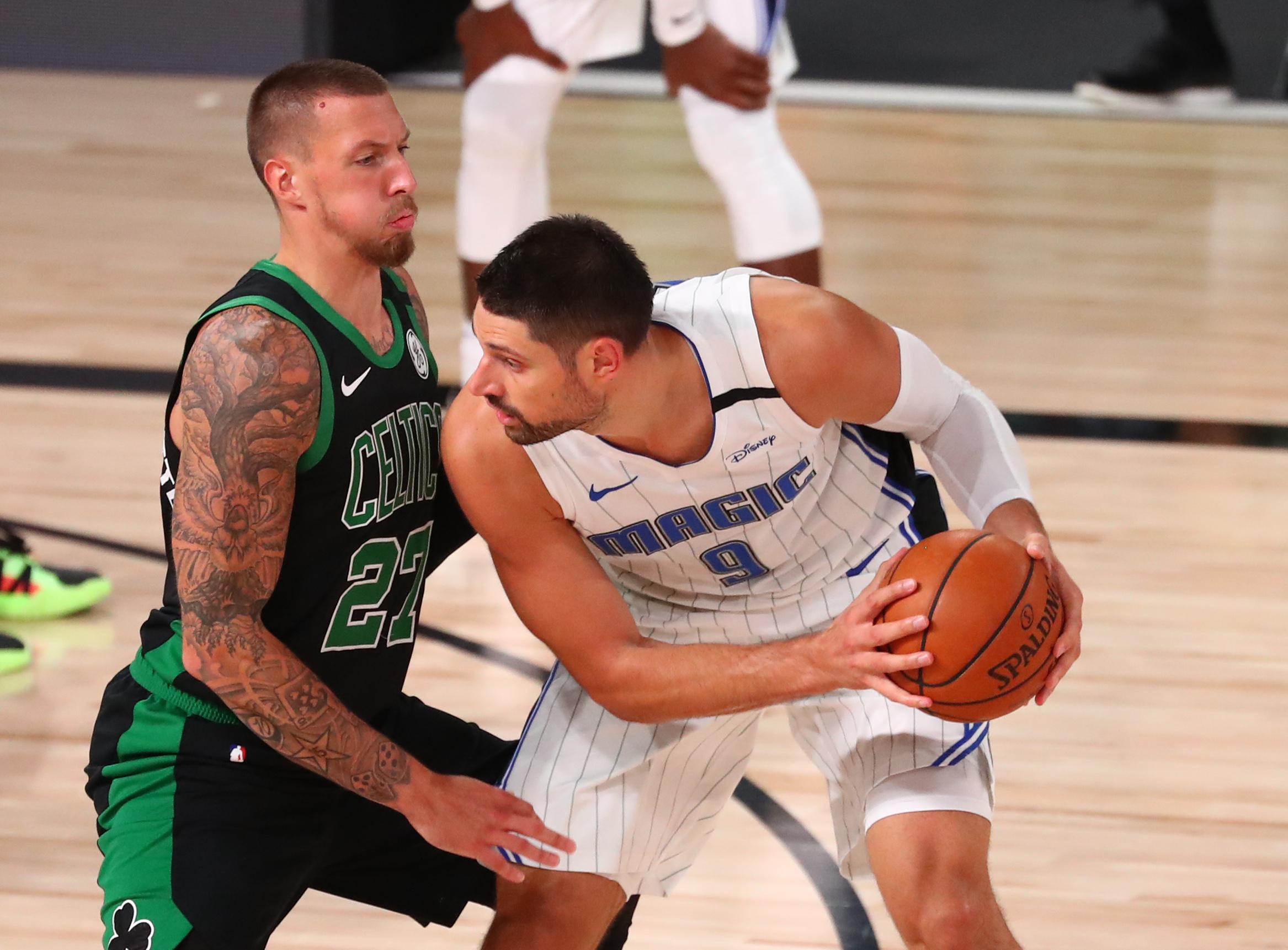 Aug 9, 2020; Lake Buena Vista, Florida, USA; Orlando Magic center Nikola Vucevic (9) controls the ball against Boston Celtics center Daniel Theis (27) during the first half of a NBA basketball game at AdventHealth Arena.