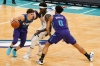 Jan 30, 2021; Charlotte, North Carolina, USA; Charlotte Hornets guard LaMelo Ball (2) drives past Milwaukee Bucks guard Jrue Holiday (21) with help from forward Miles Bridges (0) during the first quarter at Spectrum Center.