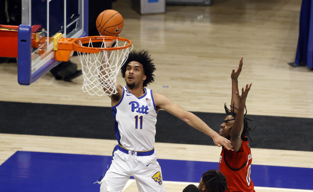 Feb 17, 2021; Pittsburgh, Pennsylvania, USA; Pittsburgh Panthers forward Justin Champagnie (11) shoots past North Carolina State Wolfpack forward DJ Funderburk (0) during the first half at the Petersen Events Center.