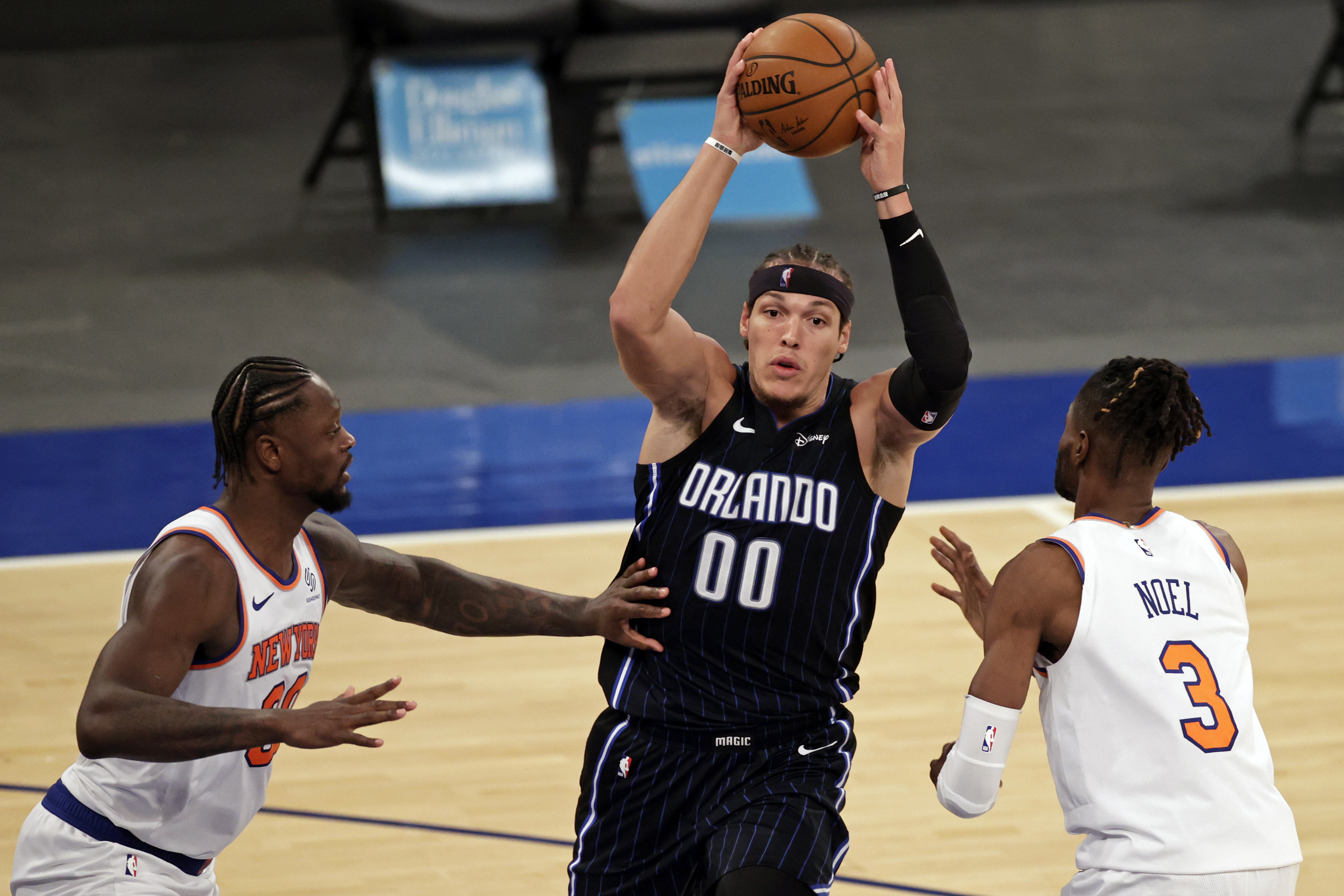 Mar 18, 2021; New York, New York, USA; Orlando Magic forward Aaron Gordon (00) looks to pass between New York Knicks forward Julius Randle and center Nerlens Noel (3) during the second half of an NBA basketball game Thursday, March 18, 2021, in New York.