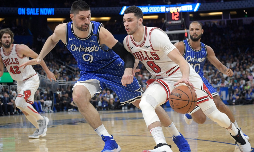 Chicago Bulls guard Zach LaVine (8) drives to the basket in front of Orlando Magic center Nikola Vucevic (9) during the second half of an NBA basketball game Friday, Feb. 22, 2019, in Orlando, Fla.
