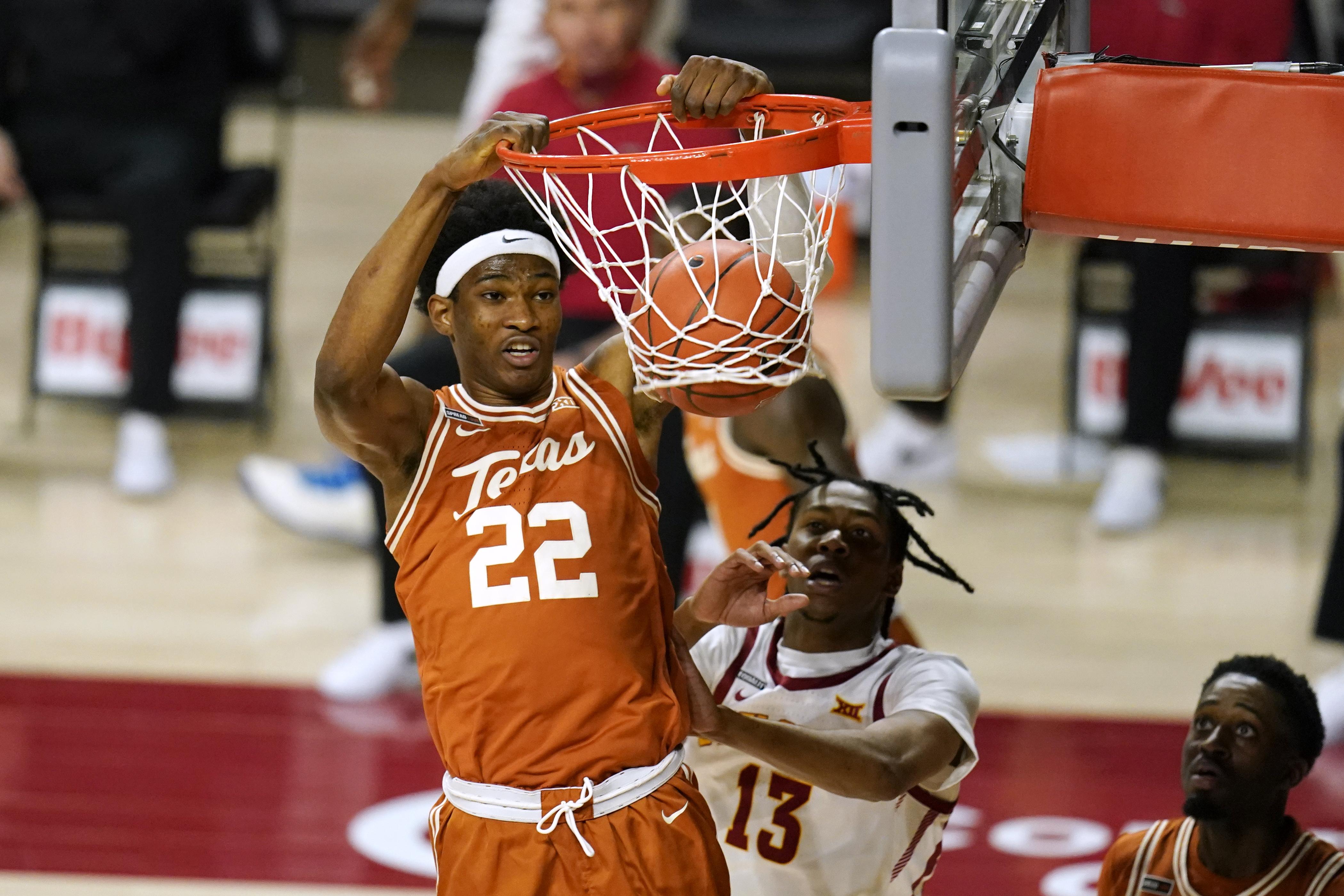 Texas forward Kai Jones (22) dunks the ball ahead of Iowa State forward Javan Johnson (13) during the first half of an NCAA college basketball game, Tuesday, March 2, 2021, in Ames, Iowa.