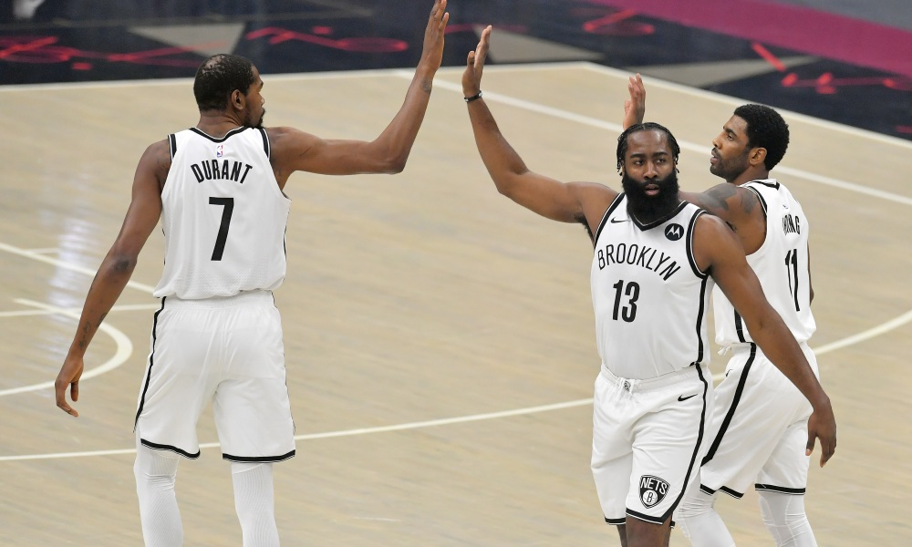CLEVELAND, OHIO - JANUARY 20: Kevin Durant #7 James Harden #13 and Kyrie Irving #11 of the Brooklyn Nets celebrate during the first quarter against the Cleveland Cavaliers at Rocket Mortgage Fieldhouse on January 20, 2021 in Cleveland, Ohio. NOTE TO USER: User expressly acknowledges and agrees that, by downloading and/or using this photograph, user is consenting to the terms and conditions of the Getty Images License Agreement.