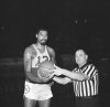 Wilt Chamberlain of the Philadelphia 76ers, who became the second player in the history of the NBA to score 20,000 points, accepts the ball from referee Willie Smith as game with New York Knicks was halted in Philadelphia, Jan. 2, 1965. Presentation was made after Chamberlain sank foul shot for 20,000th point. Chamberlain hopes to surpass the all-time point scoring record of 20,880, held by Bob Pettit, St. Louis Hawks star, before the season ends. 76ers won the game, 133-122.