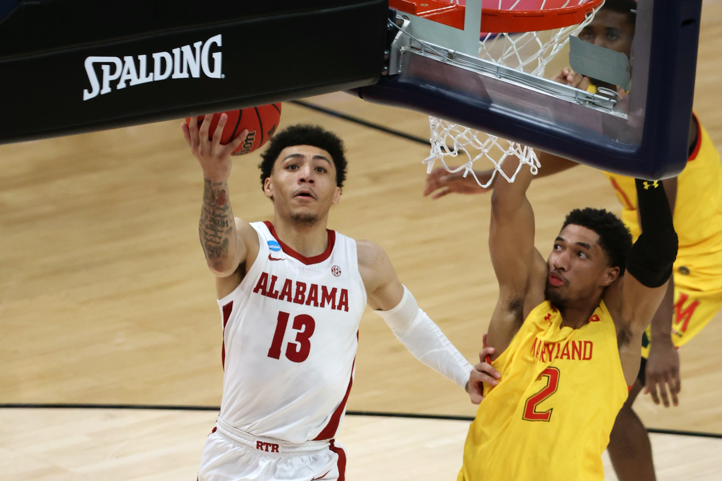 Mar 22, 2021; Indianapolis, Indiana, USA; Alabama Crimson Tide guard Jahvon Quinerly (13) shoots against Maryland Terrapins guard Aaron Wiggins (2) in the second half in the second round of the 2021 NCAA Tournament at Bankers Life Fieldhouse.