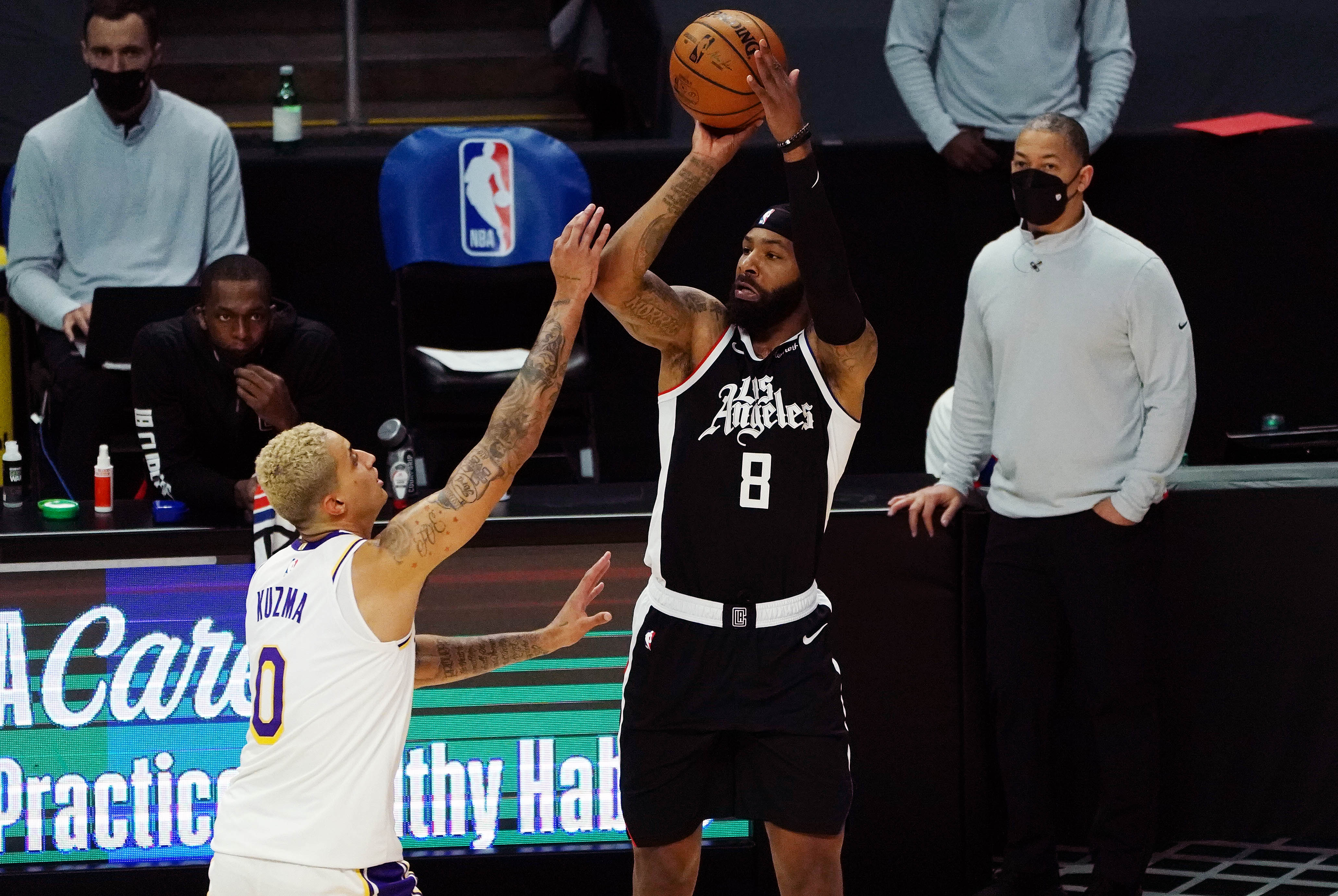 Apr 4, 2021; Los Angeles, California, USA; Los Angeles Clippers forward Marcus Morris Sr. (8) shoots against Los Angeles Lakers forward Kyle Kuzma (0) during the first half at Staples Center.