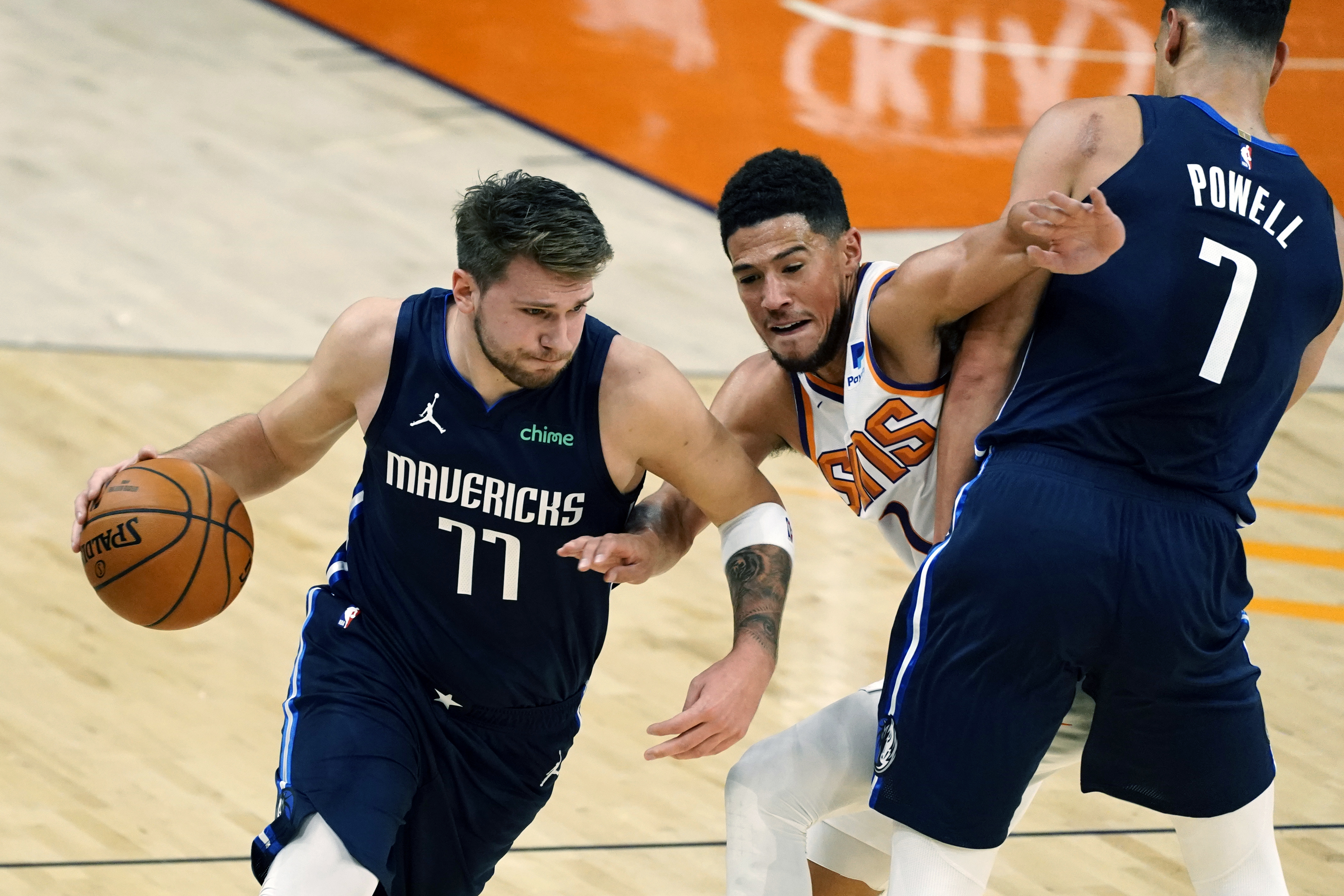 Dallas Mavericks guard Luka Doncic (77) uses the pick by Dwight Powell (7) to drive past Phoenix Suns guard Devin Booker during the first half of an NBA basketball game Wednesday, Dec. 23, 2020, in Phoenix.