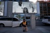 Randolf Garrido, 25, kneels in front of a sign commemorating Kobe Bryant to pay his respect as a large screen shows a commercial featuring Bryant with his daughter, Gianna, and WNBA player Sabrina Ionescu near Staples Center in Los Angeles, Tuesday, Jan. 26, 2021. Bryant, his daughter, Gianna, and the other seven people who climbed aboard that helicopter on a Sunday morning in Southern California have been gone for one year now. Tuesday marks the grim anniversary of the crash that took their lives.
