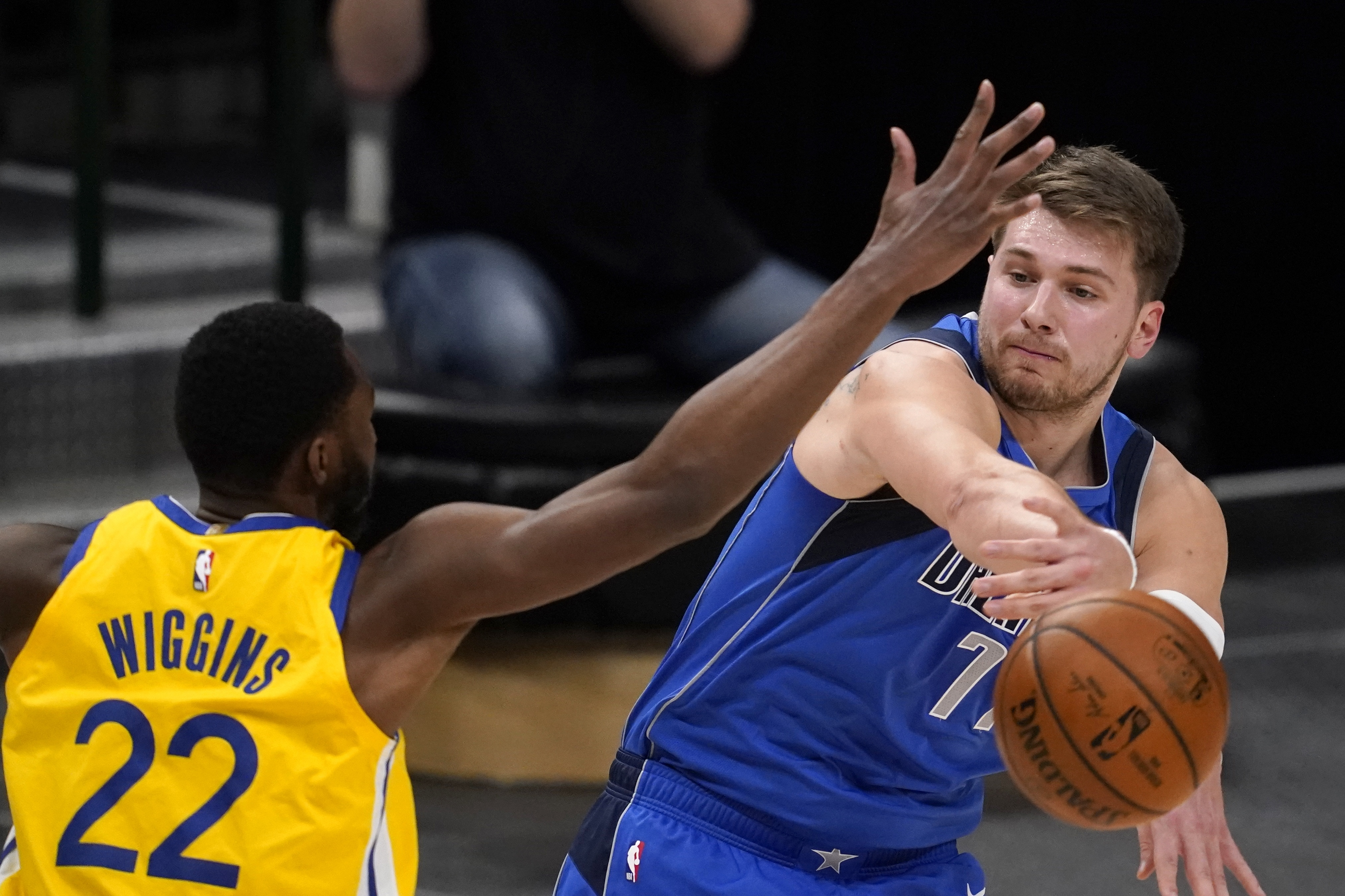 Golden State Warriors' Andrew Wiggins (22) defends against a pass by Dallas Mavericks' Luka Doncic during the first half of an NBA basketball game in Dallas, Thursday, Feb. 4, 2021.