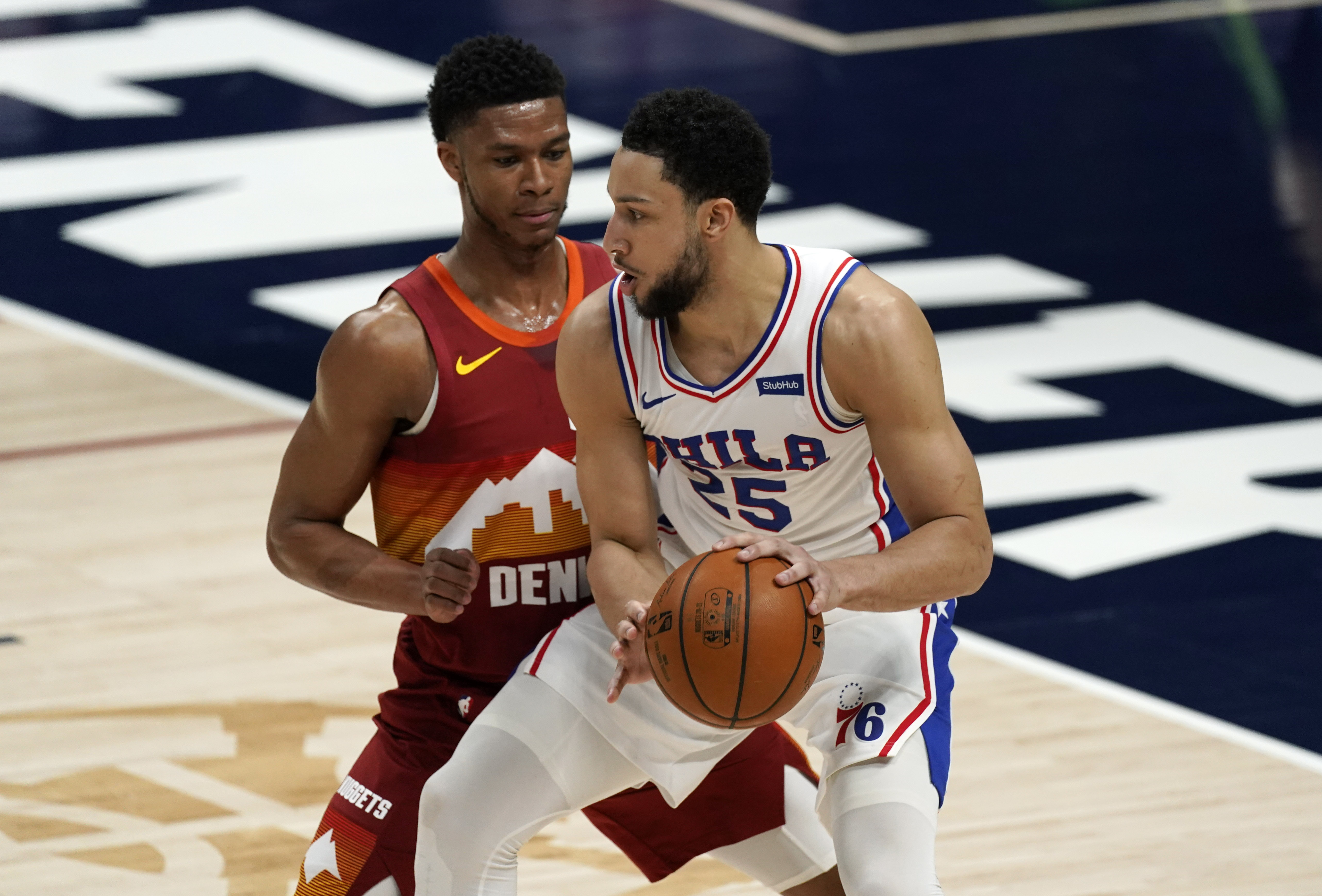 Philadelphia 76ers guard Ben Simmons, front, moves to the rim as Denver Nuggets guard PJ Dozier defends in the first half of an NBA basketball game Tuesday, March 30, 2021, in Denver.